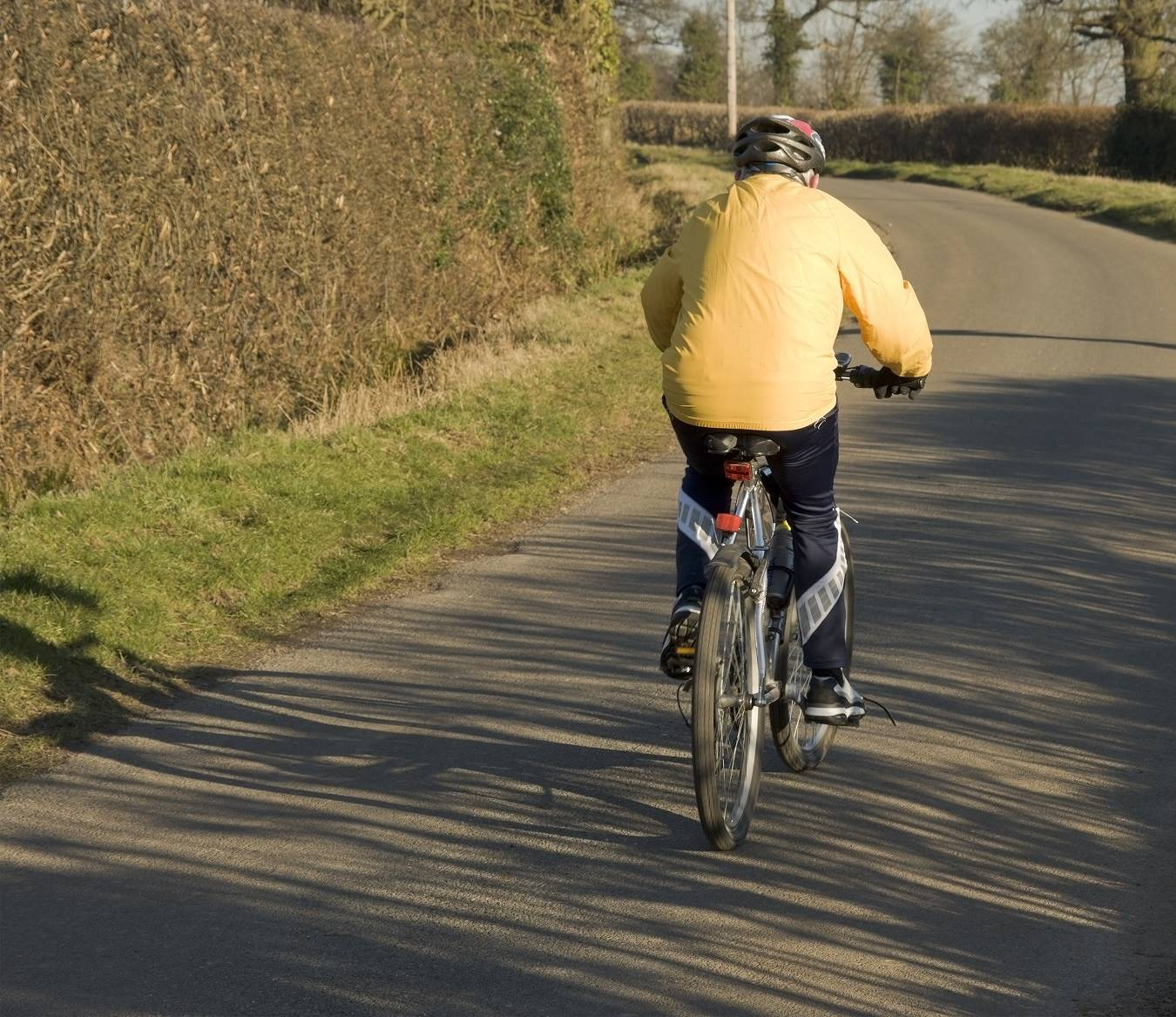 A senior cyclist cycling along road