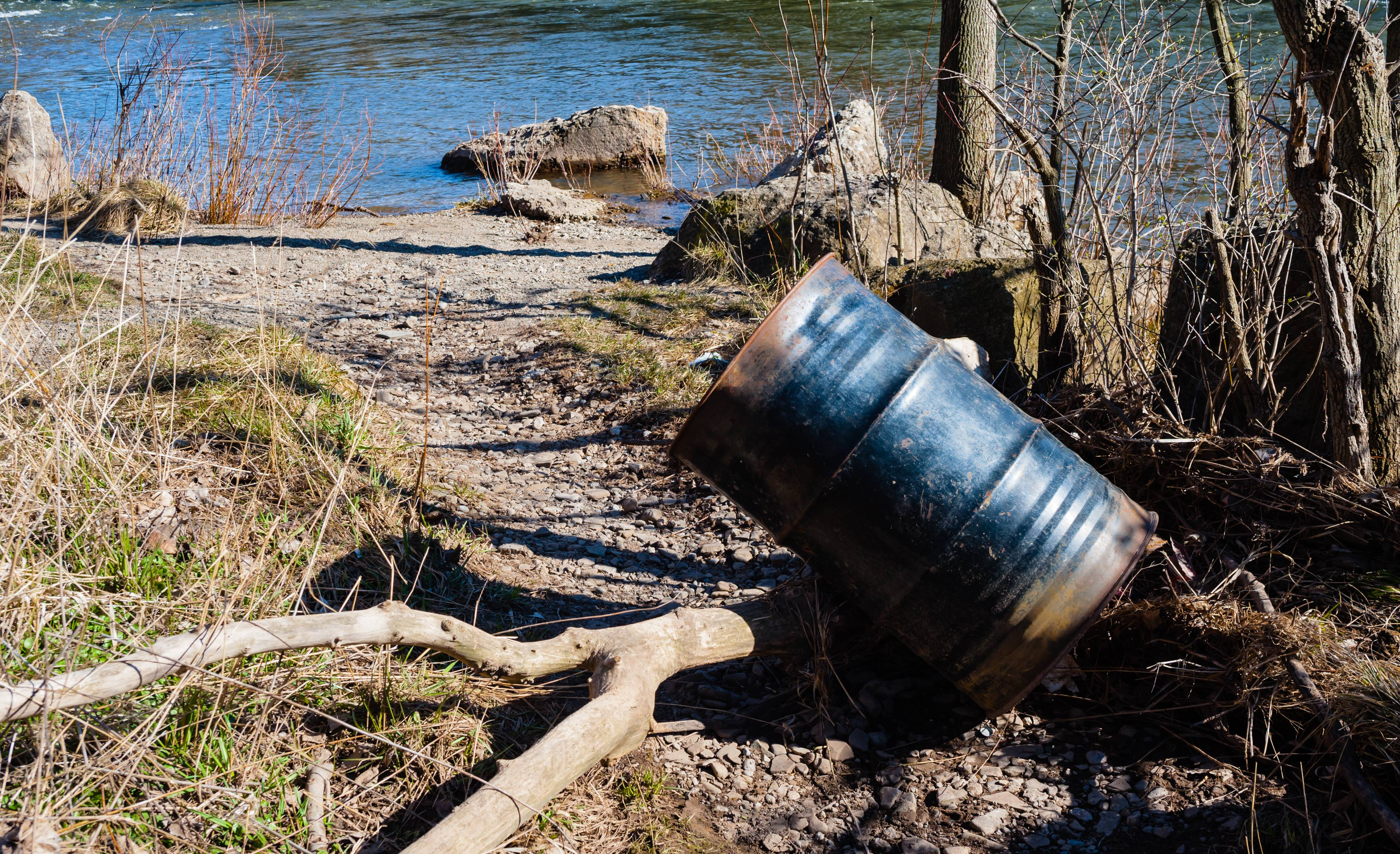 Partly rusted metal garbage can or drum leaning on branch on gravel path near river.